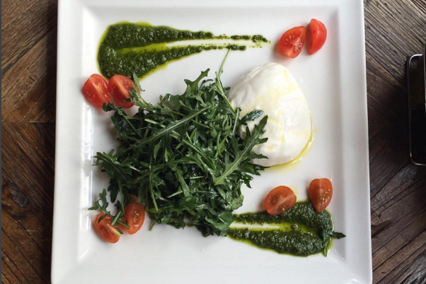 Burrata plated with pesto at The Hamptons Cafe Dubai