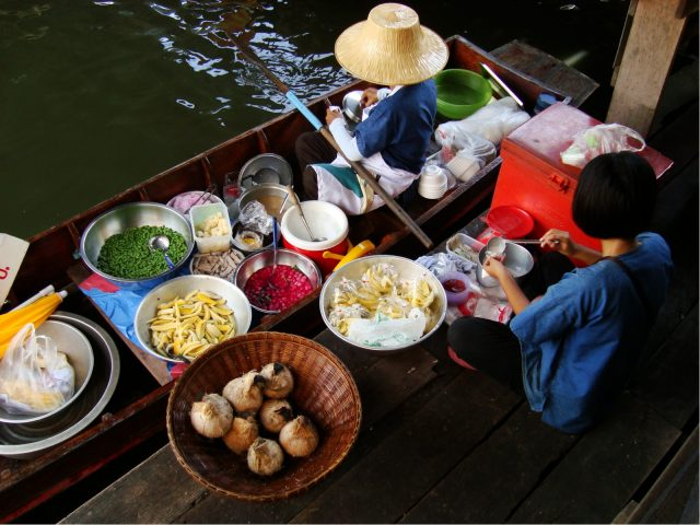 Women cooking food at a floating market in Bangkok